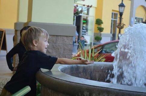 boy autism playing in fountain